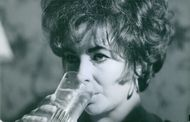 A pretty woman drinking a glass of water.