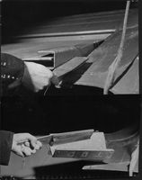 Two photos showing the function of a KLM rudder lock on a Douglas plane.