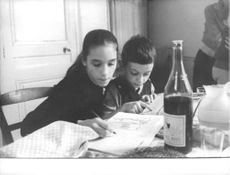 Joëlle Jacque with a little boy doing their homework at the dining table.