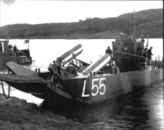 One of the Navy's landing boats ashore wreckage of the helicopter.