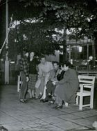 Men and women gathered together. A woman seen smoking a cigarette.