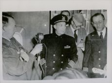 Captain William E. Donohue being interviewed on board his ship. On the right is Commander James A. Barnes. 1952.