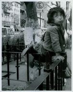 A young boy living in the sides of the street.