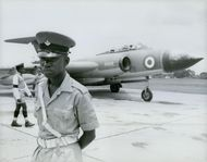 A military officer guarding the jet plane at the airport tarmac in Zambia. 1965.
