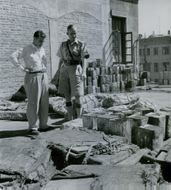 A soldier pointing a different types of materials on the ground.