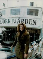 Cindy Crawford holds on to the rails of the ship as she smiles for the camera.