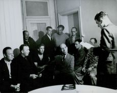 Group of men gathered in one room.