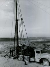 Two men working on the oil drilling.