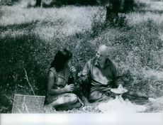 A man and a woman siting while having a picnic in the field.