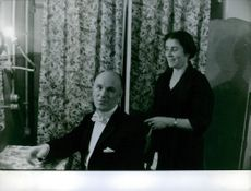 A man siting in the chair while his wife standing looking at him.