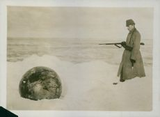 Soldier standing while looking the cannon ball in the snow during Tyskland war.