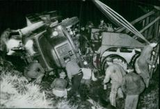 The rescue team in febrile operations to save injured by means of salvage cranes after a lorry rolled down the road