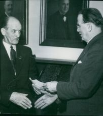 Dir. F. Grahn Lund hands over a check to the man who found the greater part of the spoils at bilkuppen in Örebro. The man got 10% of the re-acquired amount.