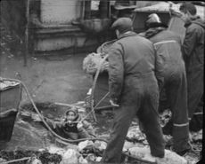 A grodman walks into the muddy water to search for the dead worker Algot Möller after a raid accident on the Skåne cement foundry