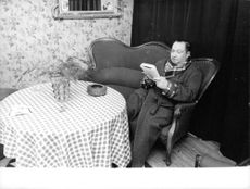 Joseph Joanovici reading a book on a couch.