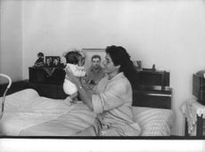 Irène Jodard holding baby, sitting on bed, August 1960.