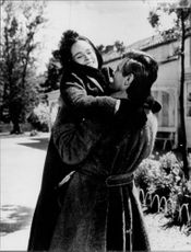 Geraldine Chaplin embraced by man.