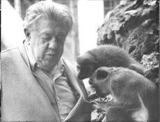Michel Simon standing beside of the monkey.