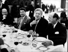 Michel Simon smiling, sitting at table.