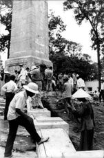 Vietnamese working on building a structure supervised by an American.
