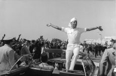 King Hassan II waves his hands to the crowd.