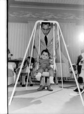 Hassan II of Morocco being photographed playing with his child sitting on rocking cradle