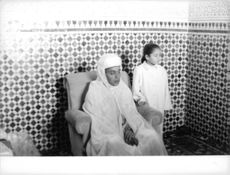 Hassan II of Morocco sitting on the chair.