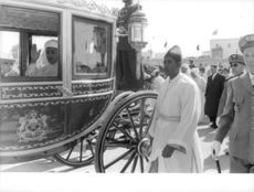 King Hassan II of Morocco is about to enter his royal carriage.