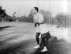King Hassan II holding a tennis racket.
