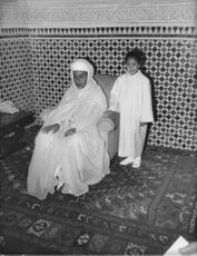 Hassan II seated.