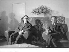 King Hassan II sitting with a man and facing camera.
