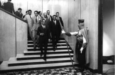 King Hassan II and his staff walking inside a building.