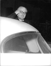 John Russell, 13th Duke of Bedford, leaning on the hood of the car.