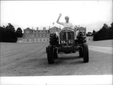 John Russell, 13th Duke of Bedford, riding the tractor.