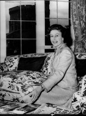 Queen Elizabeth II sits on the couch and goes through the old newspaper she saved.