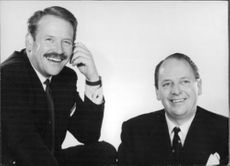 David and John Wickins (left with moustache) smiling.