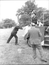 13th Duke of Bedford Ian Russell being photographed trying to pull a vehicle and his third wife Nicole Russell enjoying it standing on the vehicle