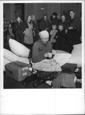 A Finnish lady being photographed sitting beside of baggage sewing something waiting for train to get away from Finland during Winter War in 1939