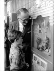 John Russell, 13th Duke of Bedford, with a young boy looking at the small sculptures.