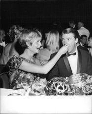 Ricky Nelson getting feed by a woman at an event.