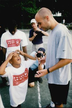 American tennis player Andre Agassi provides tennis lessons for children in Central Park