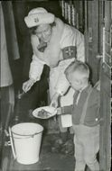 A Swedish Lotta giving a Finnish child some food. 1940