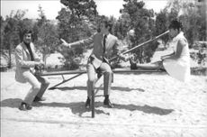 Jeanne Moreau and men sitting on see-saw.