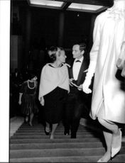 Jeanne Moreau walking up stairs with man.