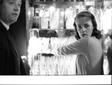 Jeanne Moreau by glass cabinet looking back.