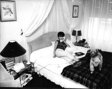 Jeanne Moreau on the phone, lying on bed.