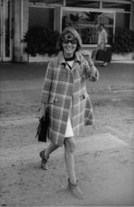 Jeanne Moreau, with sunglasses, walking and smiling.