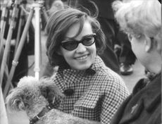 Jeanne Moreau with sunglasses and dog smiling.
