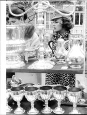 Jeanne Moreau standing by display of silver ware.