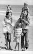 Lesley-Anne Down and Don E. Fauntleroy walk on the beach with their children